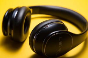 Črne bluetooth slušalke na rumeni podlagi.