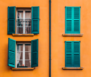 Bela okna s turkiznimi polkni na ornažni hiši. Dva okna sta odprta, dva zaprta.