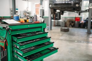 Voziček za orodje v zeleni barvi na sredi delavnice.